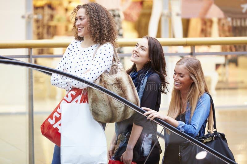 Tre kvinnliga vänner som tillsammans shoppar i galleria arkivbilder