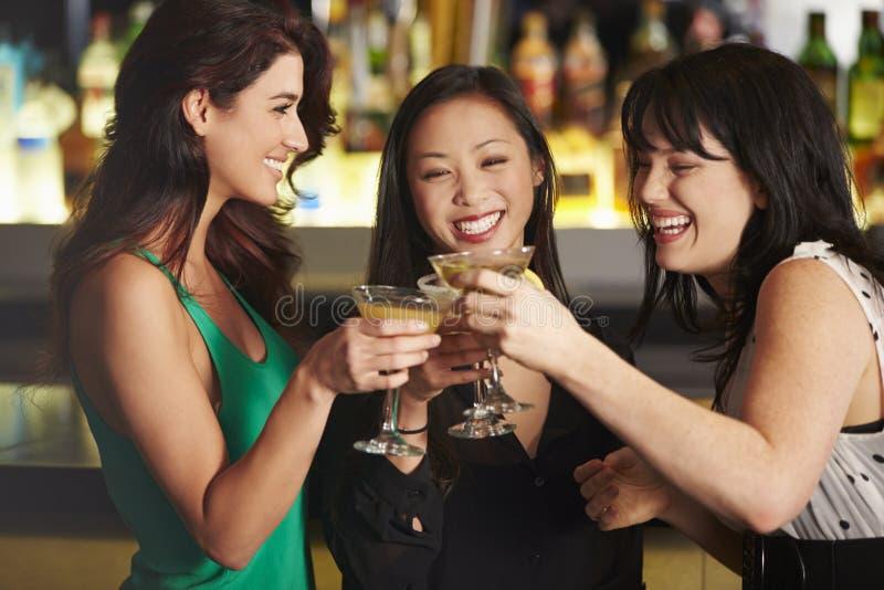 Tre kvinnliga vänner som tycker om drinken i coctailstång arkivfoto