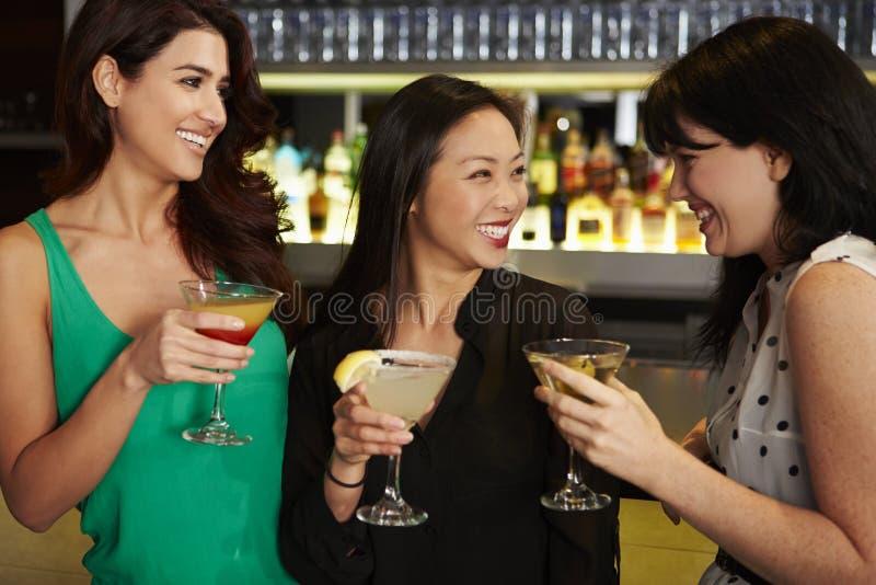 Tre kvinnliga vänner som tycker om drinken i coctailstång arkivbild