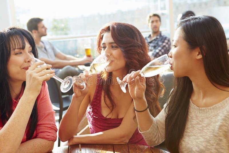 Tre kvinnliga vänner som tycker om drinken på den utomhus- takstången fotografering för bildbyråer