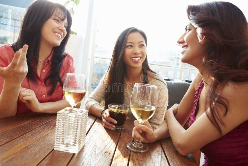 Tre kvinnliga vänner som tycker om drinken på den utomhus- takstången arkivfoto