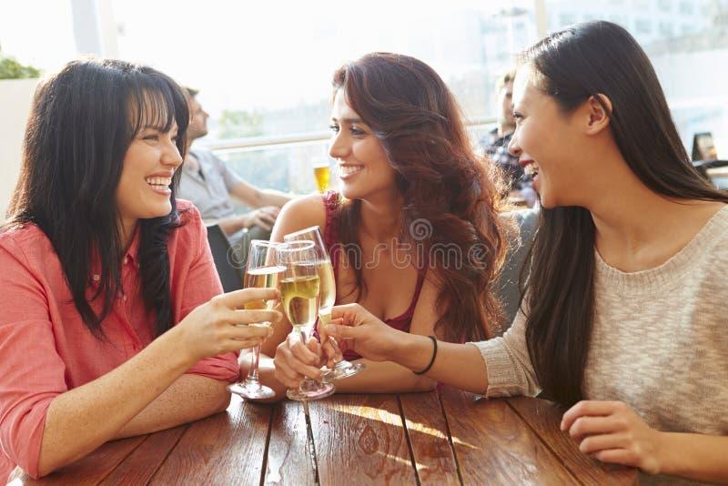 Tre kvinnliga vänner som tycker om drinken på den utomhus- takstången royaltyfri foto