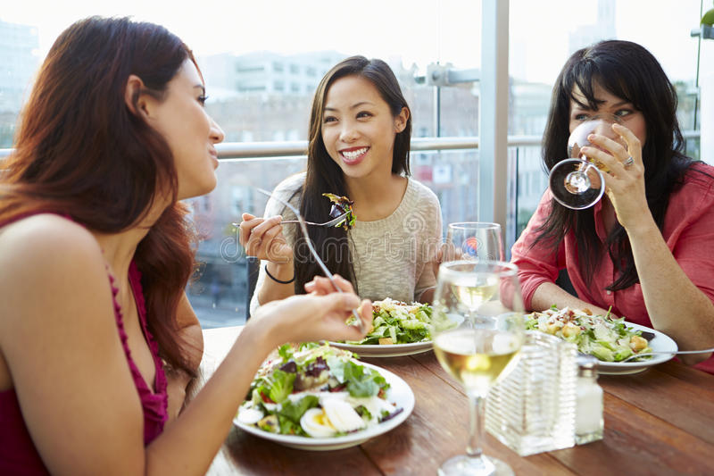 Tre kvinnliga vänner som tycker om lunch på takrestaurangen arkivfoton