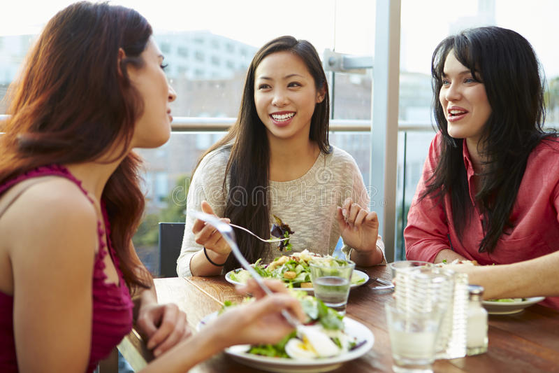 Tre kvinnliga vänner som tycker om lunch på takrestaurangen fotografering för bildbyråer