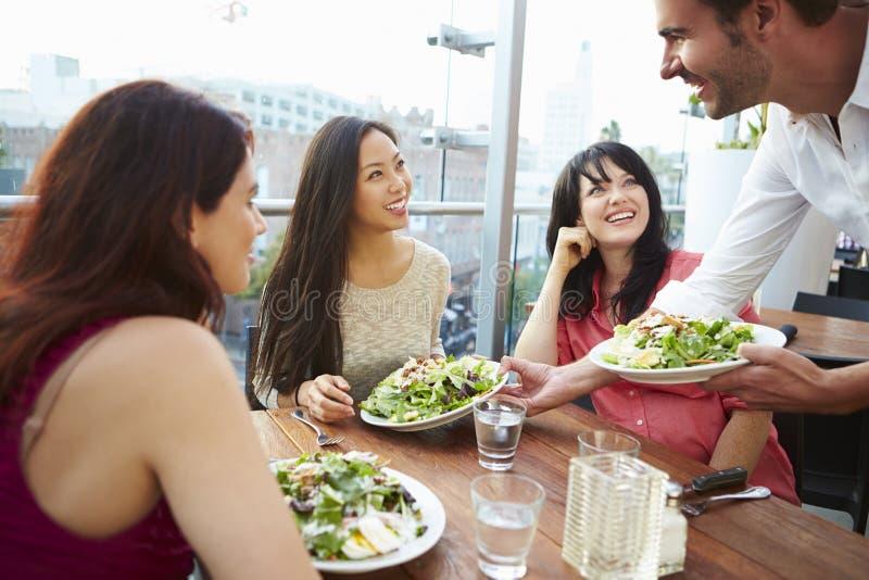 Tre kvinnliga vänner som tycker om lunch på takrestaurangen royaltyfri bild
