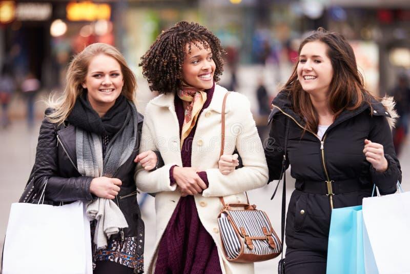 Tre kvinnliga vänner som utomhus tillsammans shoppar royaltyfri bild