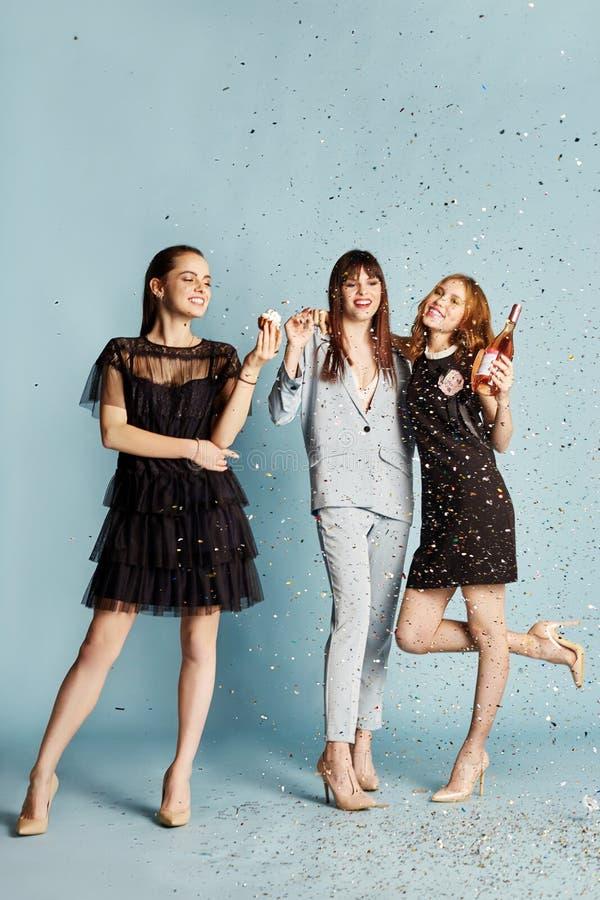 Tre kvinnor firar ferien som har gyckel som skrattar och äter kakor under flygakonfettierna Flickor som poserar och ler på blått royaltyfria bilder