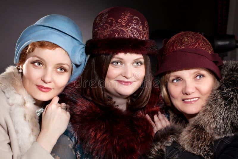Tre kvinnor fostrar, och döttrar som att ha på sig klädde med filt hattar i retro, utformar arkivfoto