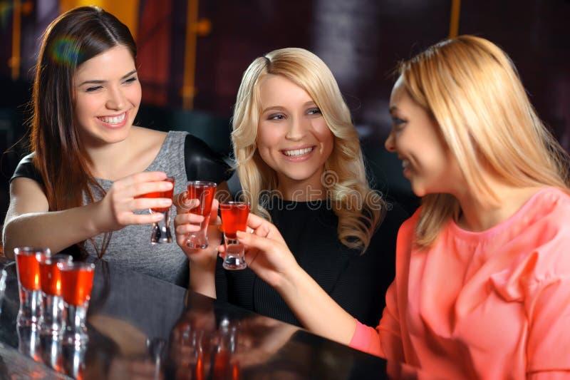 Tre kvinnor har en drink i stången arkivbilder