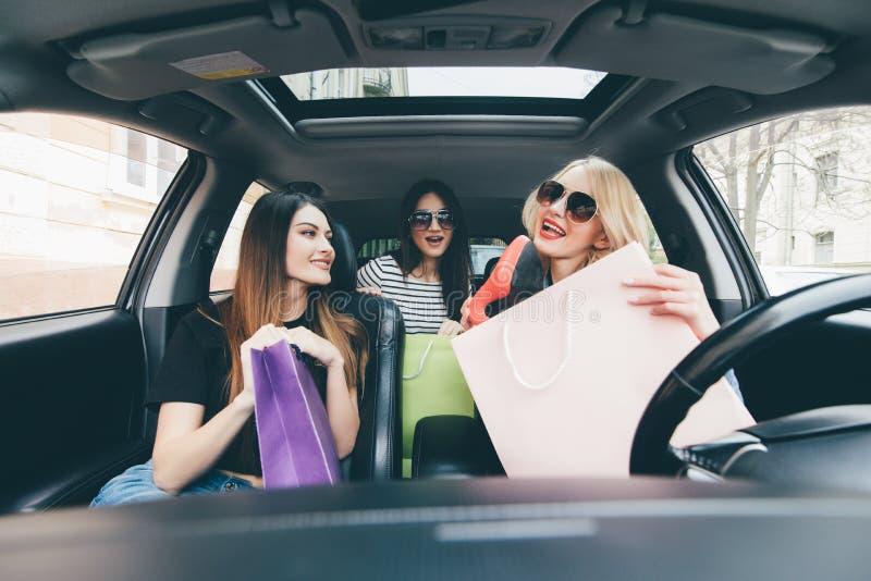 Tre kvinnor har gyckel i bilen, når de har shoping och visar nya köpskor arkivbilder