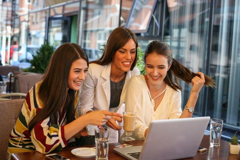 Tre kvinnor har gyckel på bärbara datorn på kafét, royaltyfri foto