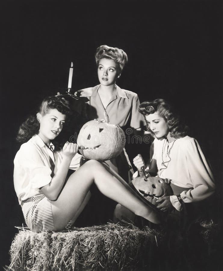 Tre kvinnor i en ladugård som snider pumpor på natten royaltyfri fotografi