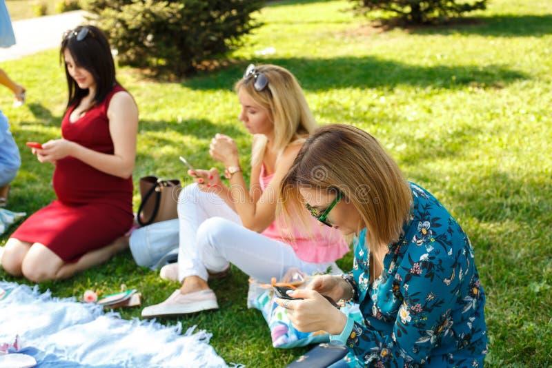 Tre kvinnor i sommargräsplan parkerar att se i deras smartphones royaltyfri fotografi