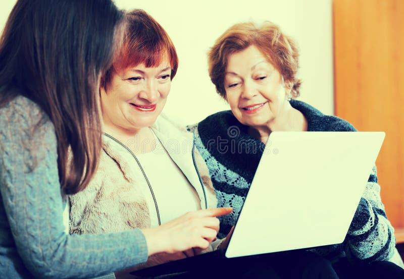 Tre kvinnor med bärbara datorn arkivfoton