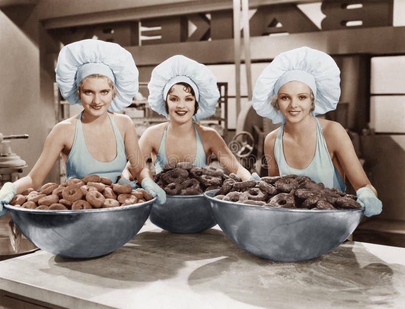 Tre kvinnor med enorma bunkar av donuts arkivbild