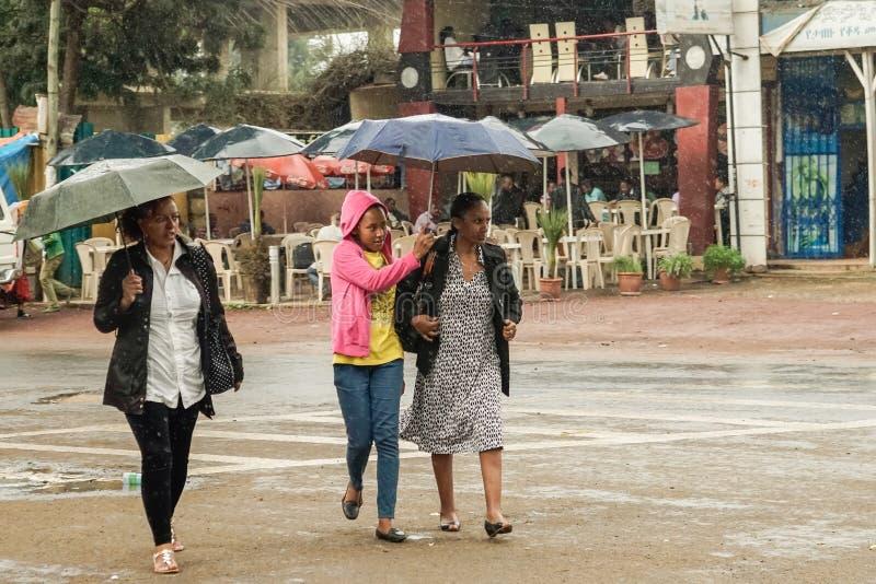 Tre kvinnor med ett paraply som in går på gatorna av Addis arkivfoto