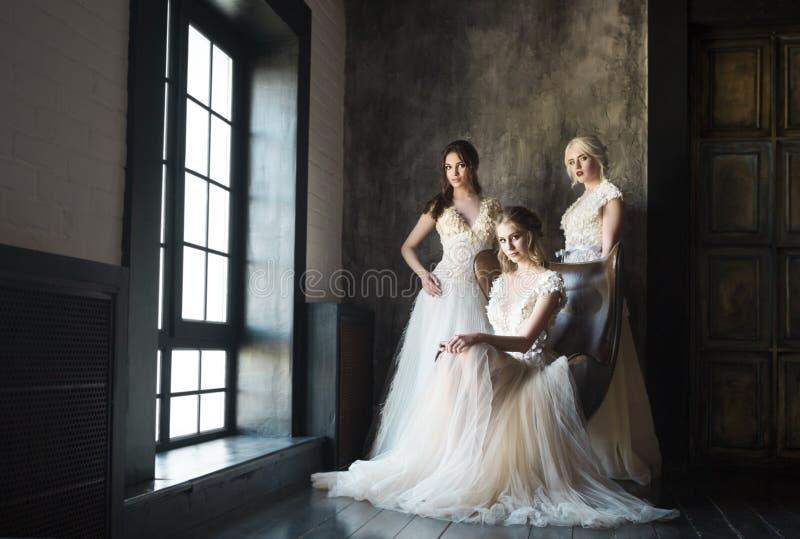 Tre kvinnor near bärande bröllopsklänningar för fönstret arkivbilder