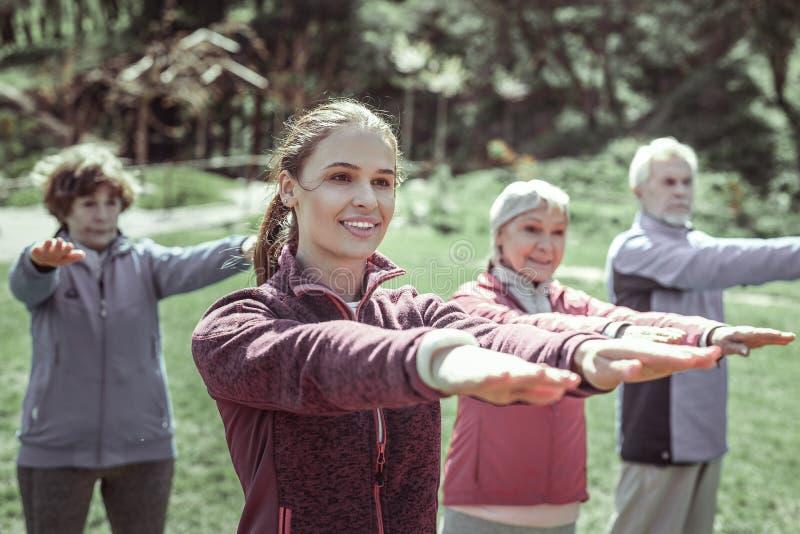 Tre kvinnor och en stilig man som gör yoga royaltyfri foto