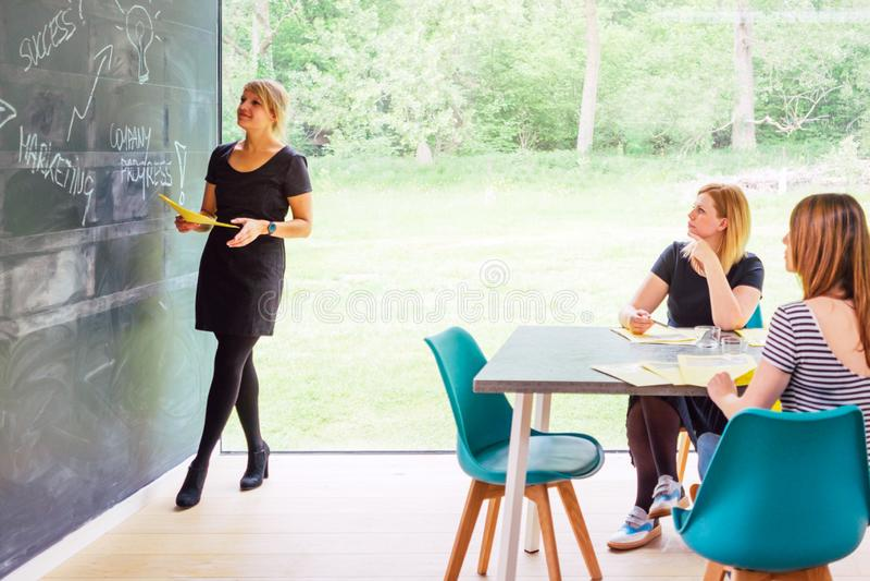 Tre kvinnor som är upptagna med ett marknadsföra seminarium arkivbilder
