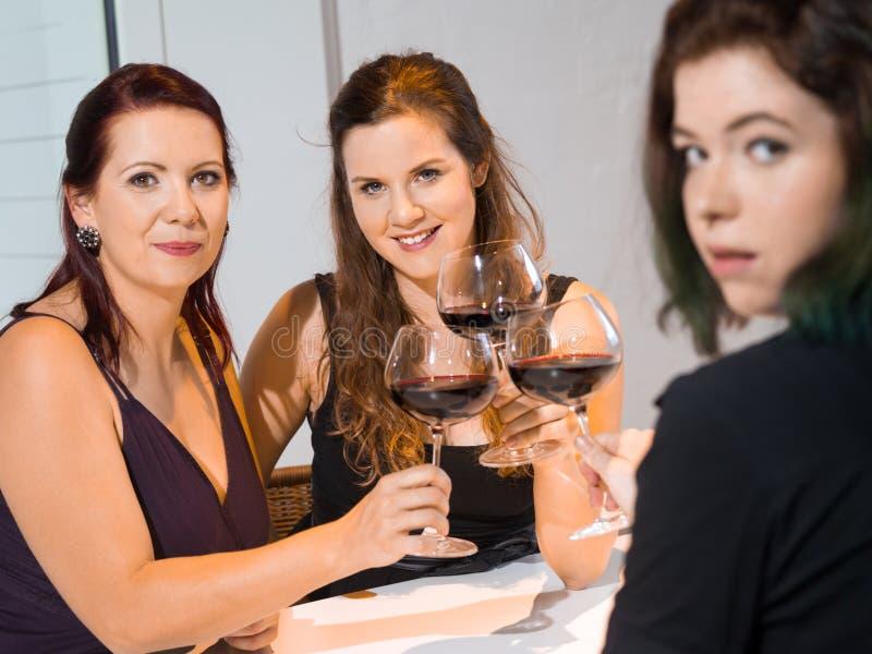 Tre kvinnor som dricker rött vin fotografering för bildbyråer