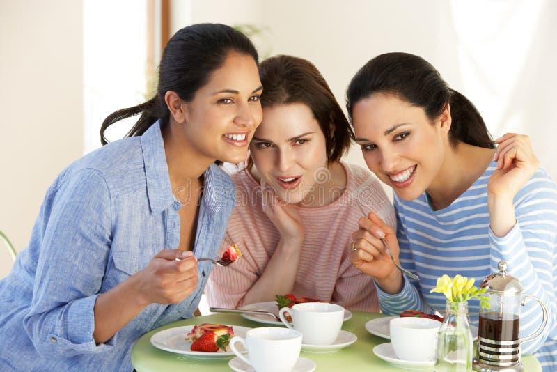 Tre kvinnor som har mellanmålet i kafé royaltyfria foton