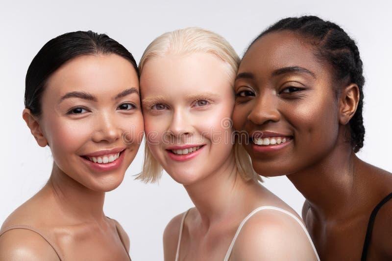 Tre kvinnor som ler, medan t?nka om kvinnamakt arkivbild