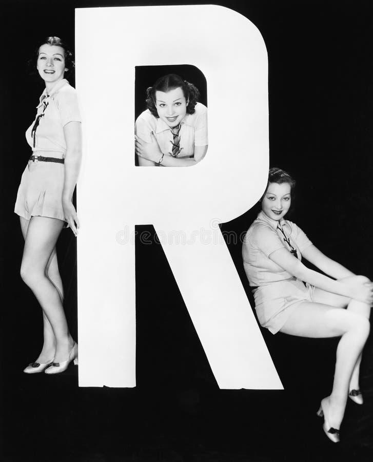Tre kvinnor som poserar med enorm bokstav R (alla visade personer inte är längre uppehälle, och inget gods finns Leverantörgarant royaltyfri bild