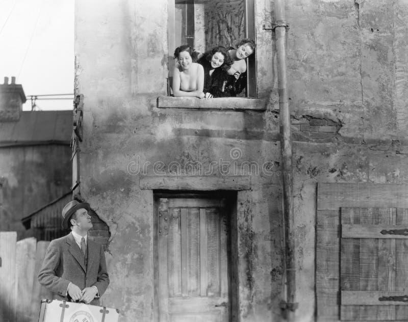 Tre kvinnor som ser ut ur ett fönster på ett mananseende i gatan med en resväska (alla visade personer inte är längre uppehälle a royaltyfri fotografi