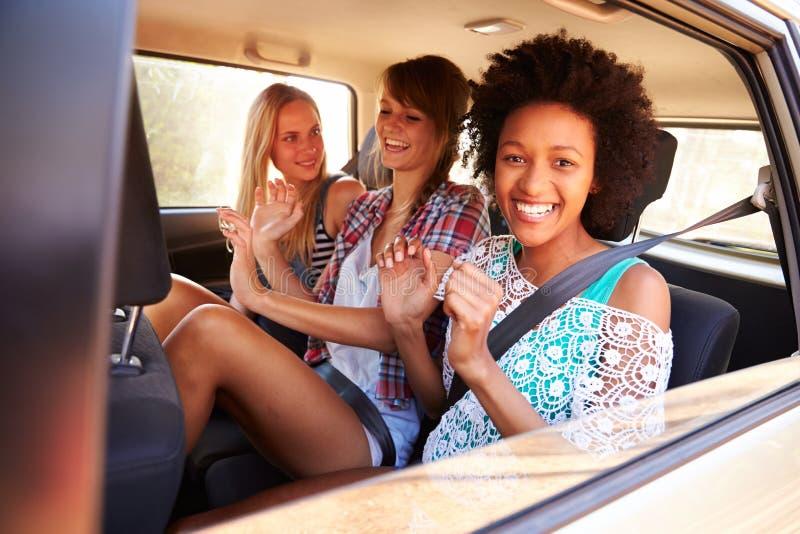 Tre kvinnor som sitter i bakre Seat av bilen på vägtur royaltyfria foton