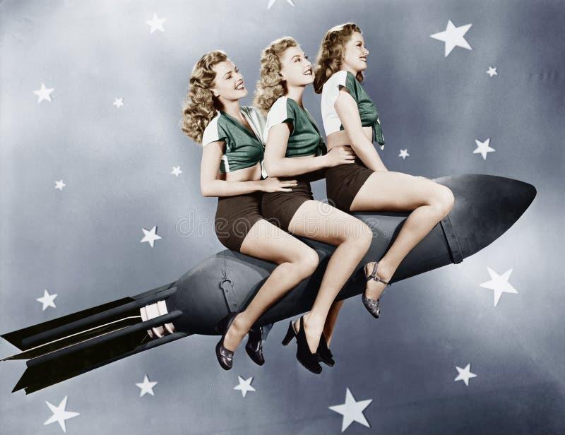 Tre kvinnor som sitter på en raket (alla visade personer inte är längre uppehälle, och inget gods finns Leverantörgarantier som d fotografering för bildbyråer