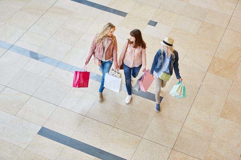 Tre kvinnor som vänner i shoppinggalleria fotografering för bildbyråer