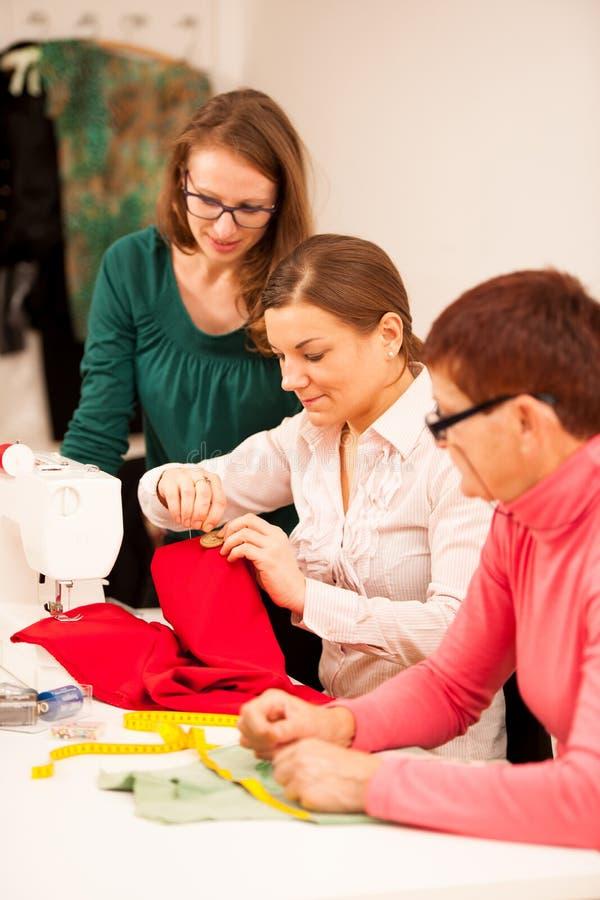 Tre kvinnor syr på handcraft seminariet De undervisar arkivbilder