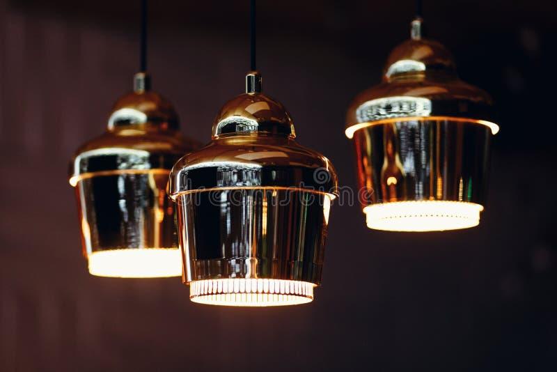 Tre lampade con l'ombra dell'oro che pende dal soffitto fotografia stock libera da diritti