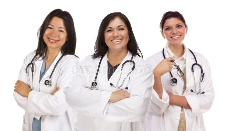 Tre latinamerikankvinnligdoktorer eller sjuksköterskor på vit royaltyfria foton