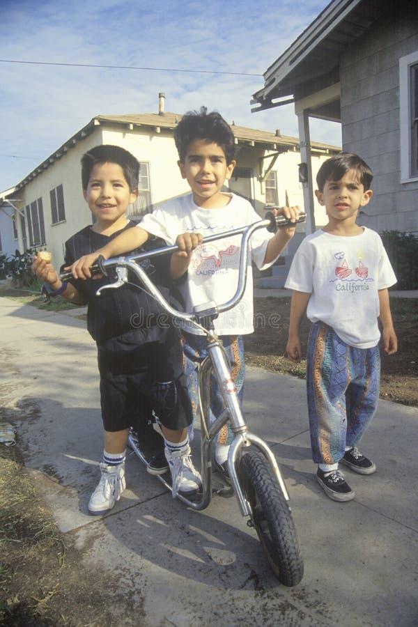 Tre Latinobarn med deras sparkcykel, Los Angeles, CA arkivbild