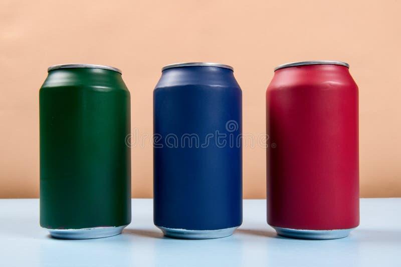 tre latte colorate delle bibite chiuse su un backgro blu-chiaro immagini stock