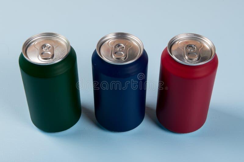 tre latte colorate delle bibite chiuse su un fondo blu-chiaro fotografia stock libera da diritti