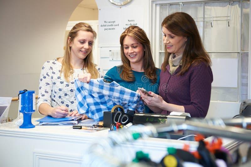 Tre lavoratori di volontari femminili nel negozio di carità immagini stock