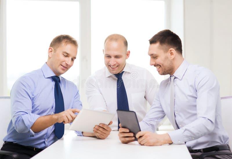 Tre le affärsmän med minnestavlaPC i regeringsställning royaltyfria bilder