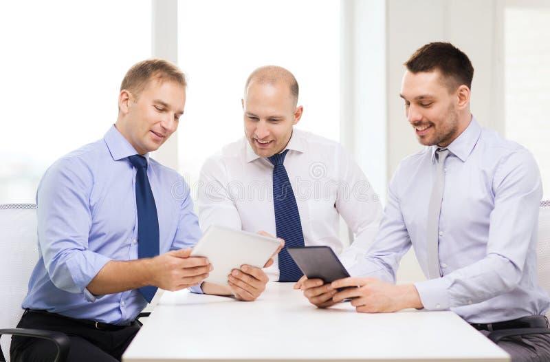 Tre le affärsmän med minnestavlaPC i regeringsställning arkivfoton