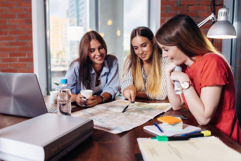 Tre le kvinnliga högskolestudenter som tillsammans arbetar på projekt i skolaarkiv arkivbild
