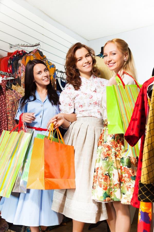 Tre le kvinnor med shoppingpåsar shoppar in arkivfoto