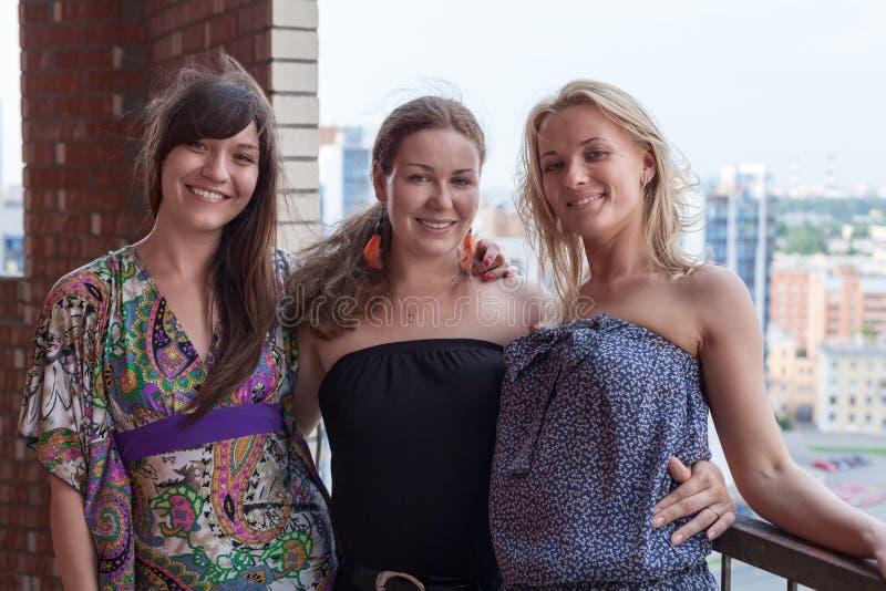 Tre le kvinnor vänner som tillsammans står och omfamnar på byggnadsbalkong royaltyfri fotografi