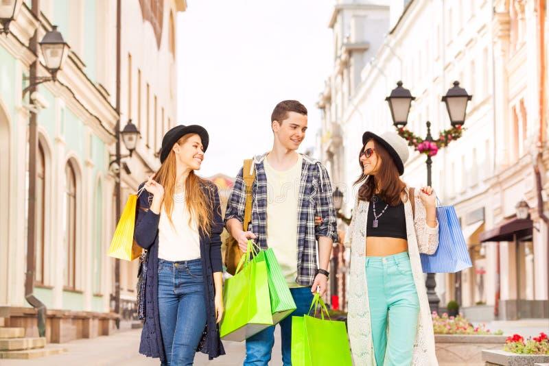 Tre le vänner som går med shoppingpåsar arkivbilder