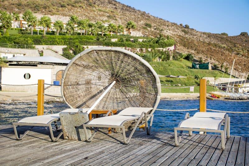 Tre lettini ed ombrelli su un pilastro di legno vicino al mare fotografia stock libera da diritti