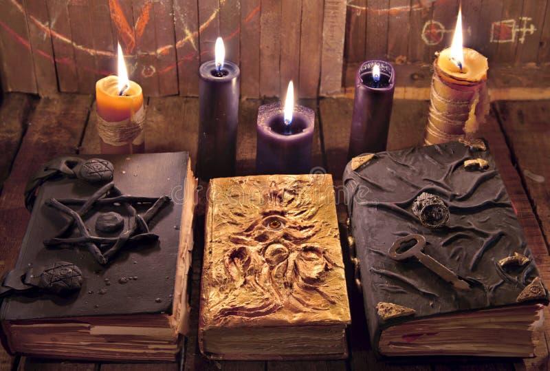 Tre libri magici con le candele brucianti sulle plance fotografia stock