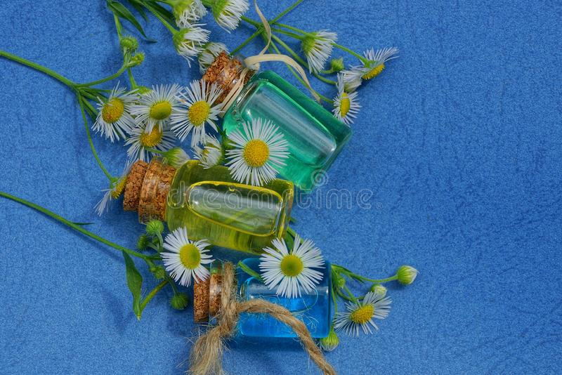 Tre lilla glasflaskor med olja bland vita tusenskönor royaltyfria foton