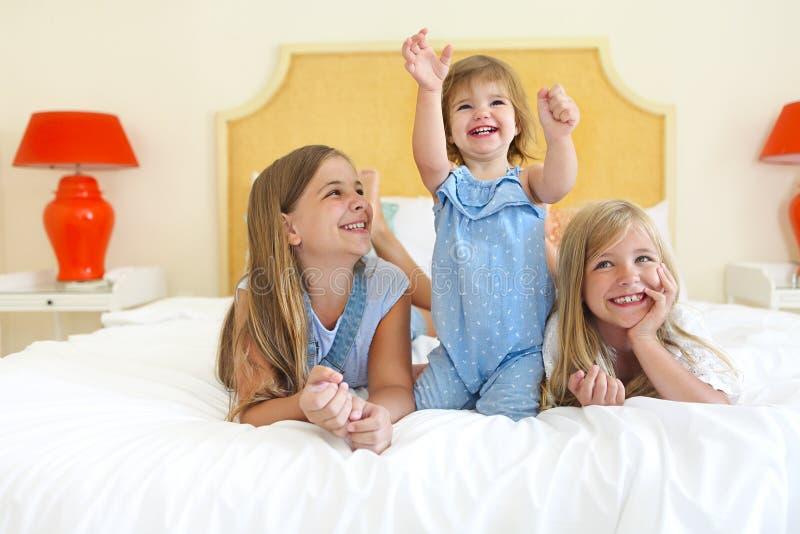 Tre lilla systrar på en säng som har gyckel royaltyfri bild