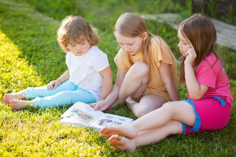 Tre lilla systrar som utomhus läser och att ha gyckel royaltyfri fotografi