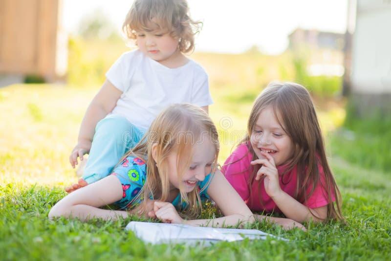Tre lilla systrar som utomhus läser och att ha gyckel arkivbild